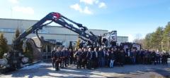 Logsetin henkilökuntaa ja Logset 12H GTE Hybrid -harvesteri tehtaalla Koivulahdessa