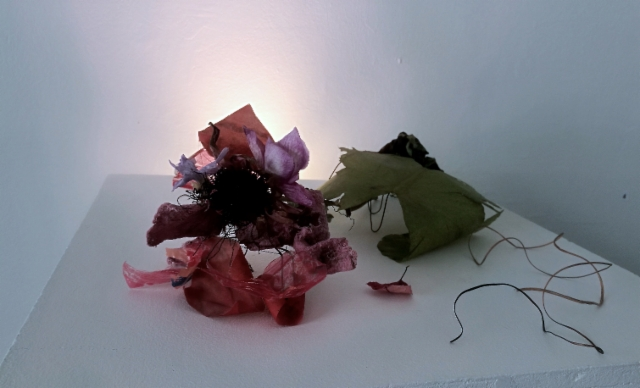 Wanna-be-rose 2018 Plants found at beaches and forests, decomposed dishcloth, fishing net sign,  parts from a grocery store´s plastic bag, plastic from an orienteering cross, steel wire   Ruusukas Wannabe Rose https://vimeo.com/331376204