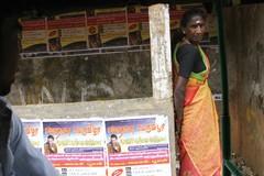 en_hindukvinna_vid_en_busshallsplats_med_posters