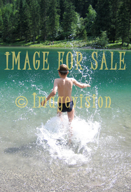 for sale child with water spatters in mountain lake