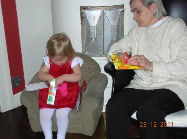 Eila-mummi ja Aino avaamassa lahjoja jouluna 2011
