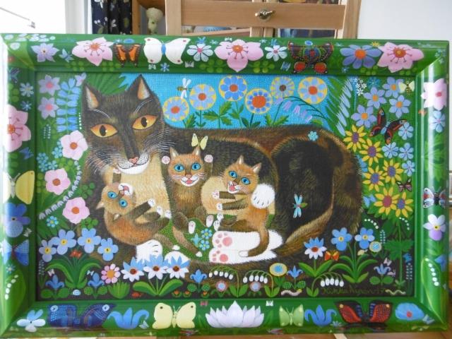 Kissaperhe kukkien keskellä