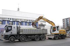 M. Juupajärven Iveco Trakker 8x4 sora-auton lava täyttyy tehokkaasti M. Nyholmin pyöräalustaisella Liebherr 316 kaivukoneella Pasilassa Ylen nurkalla