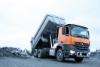 Mercedes-Benz Arocs 3351 6x4 kippaa Jorpen lavalla maanpinnalle kuljetetun noin 25 000 kilon malmikuorman kasalle.