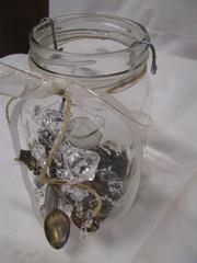 """Vanhat lusikat ja """"timantit"""" koristeena, sisällä tuikkukynttilä"""
