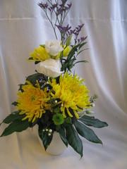 Korkea kukka-asetelma. keltasia krysanteemeja, valkoista eustomaa, lilaa limoniumia