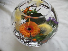 Pääsiäiskukat lasipallossa, koristeena höyheniä