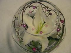 Juhlava pöytäkukka lasipallossa. Lilja, helmiä, koivunoksia