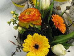 Pirteä pöytäkukka oransseista ja keltaisista kukista