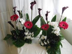 Korkeita pöytäasetelmia tummista kalloista, pinkeistä gerberoista ja valkoisista orkideoista