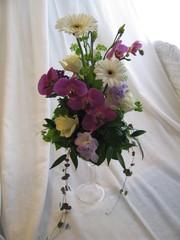 Kahvipöydän asetelma gerberoista, ruusuista, orkideoista ja freesioista.
