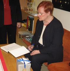 Presidentti Tarja Halonen tarkastaa vieraskirjaa