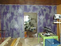Harmaa-violetti seinä kuvioineen