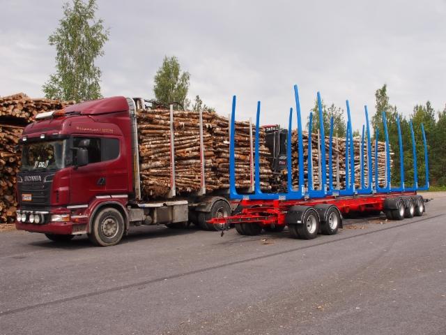 Punaisen alupankkoisen Scanian autoniput lastaantuivat täyteen nosturilovellisesta valkoisesta Scaniasta.